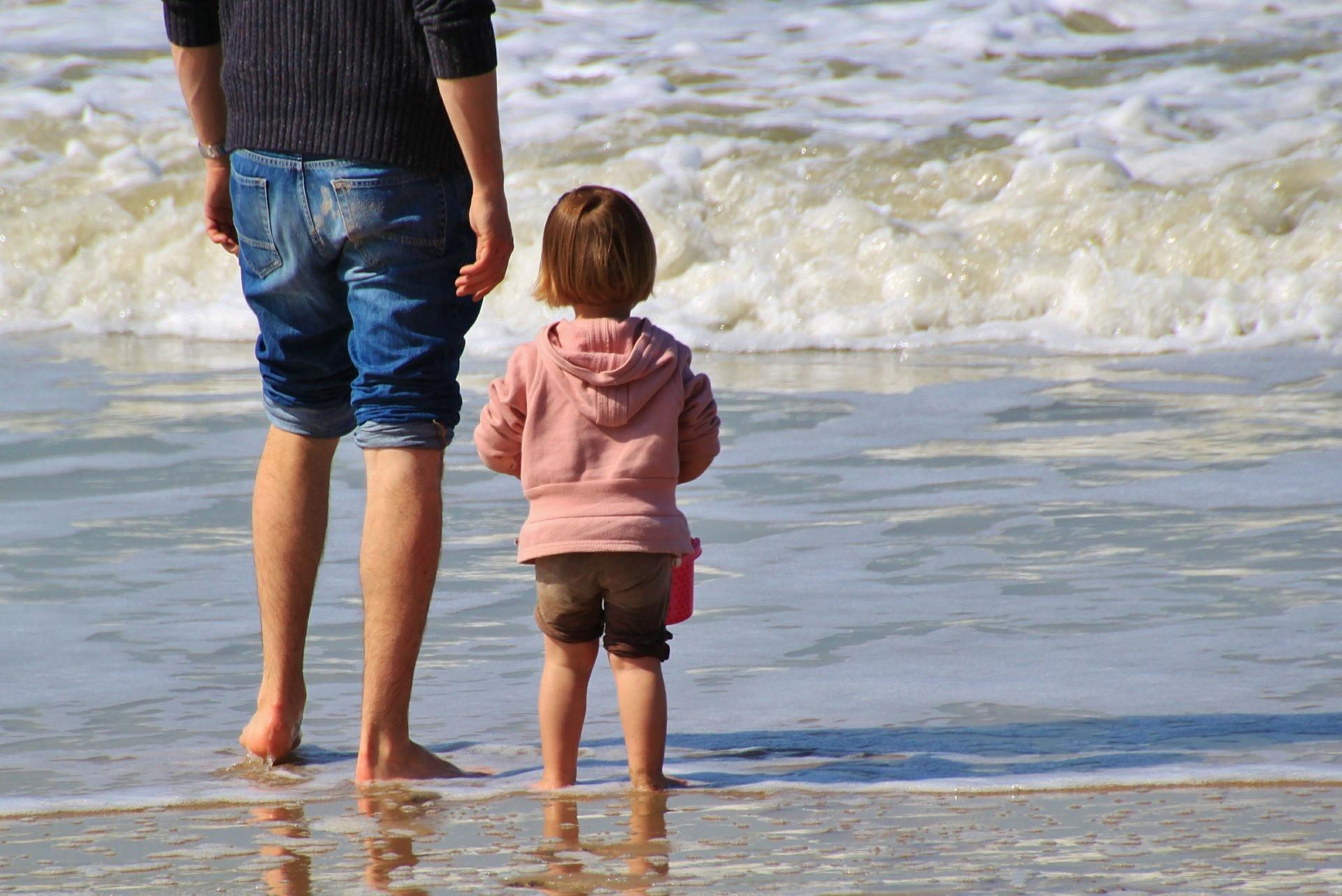 klein kind staat naast man naar de zee te kijken