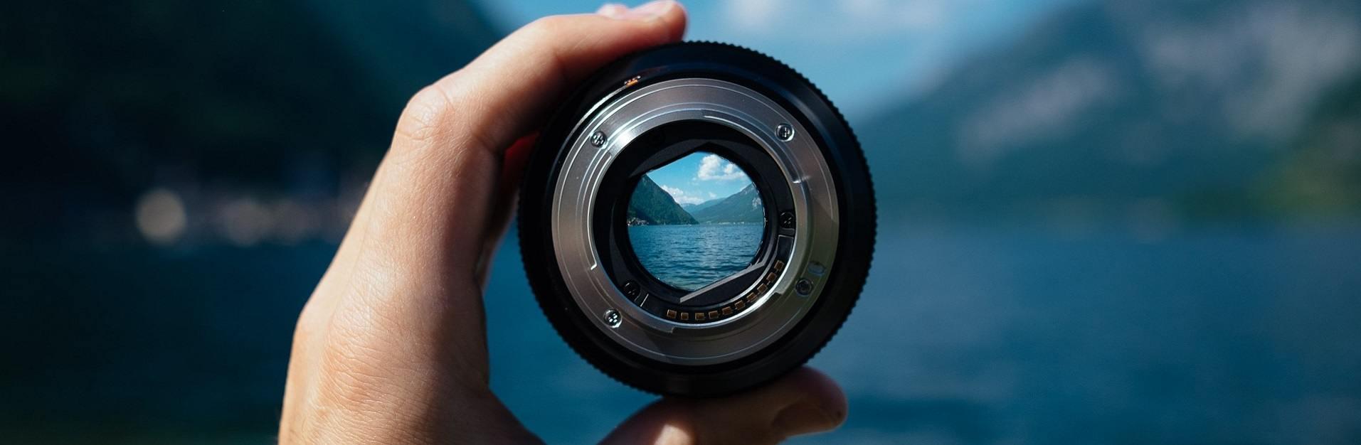 foto van hand met lens, daar doorheen zie je focus op bergen